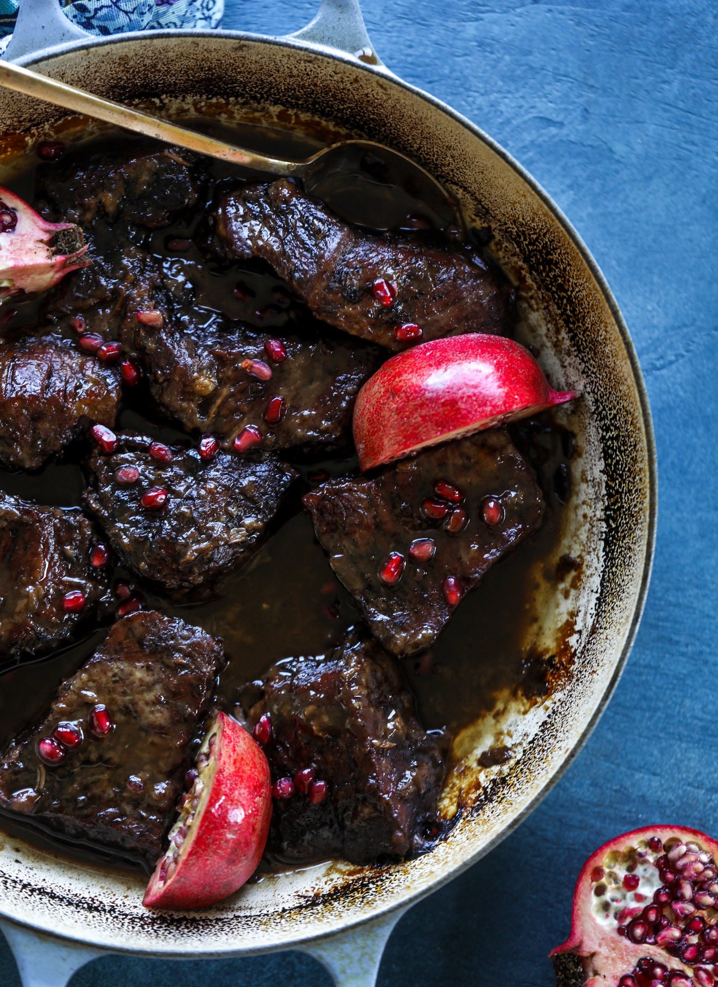 These pomegranate braised short ribs are an incredible take on comfort food! Pomegranate juice and molasses are the base of the recipe and after braising, you're left with tender, juicy and flavorful beef that is amazing served with polenta, potatoes or even in tacos. I howsweeteats.com #braised #shortribs