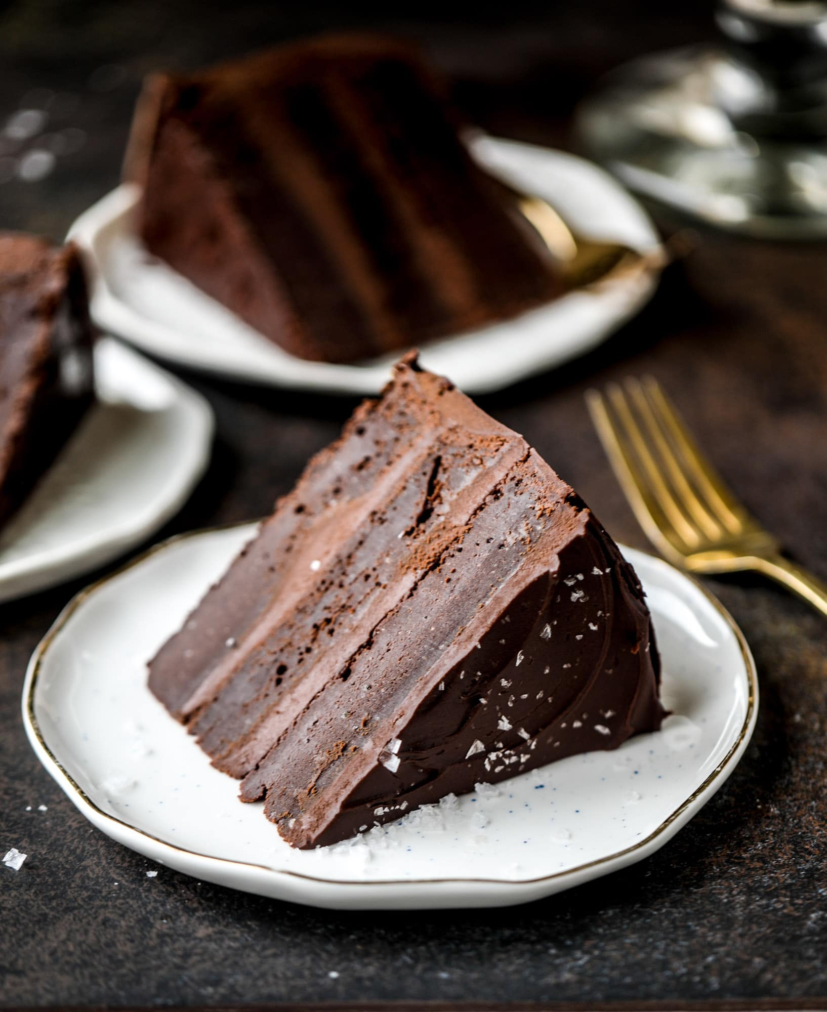 This salted dark chocolate stout cake is absolutely divine! It's ridiculously rich and perfect for a crowd or a party. Pumpkin stout batter is baked into fluffy laters and covered in a super fudgy chocolate ganache. Perfect for chocolate lovers! I howsweeteats.com #dark #chocolate #stout #cake #salted
