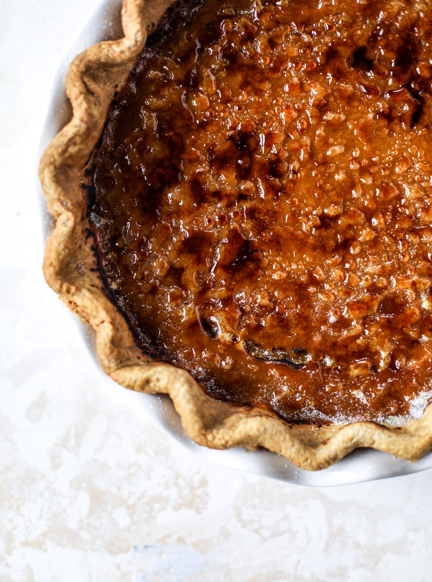 This brûlée pumpkin pie is the best of both worlds in pumpkin desserts! A delicious flaky crust, a creamy pumpkin filling and a crunchy, crispy topping - brûléed sugar right before serving. It's a whole new way to serve pumpkin pie! I howsweeteats.com #pumpkinpie #brulee