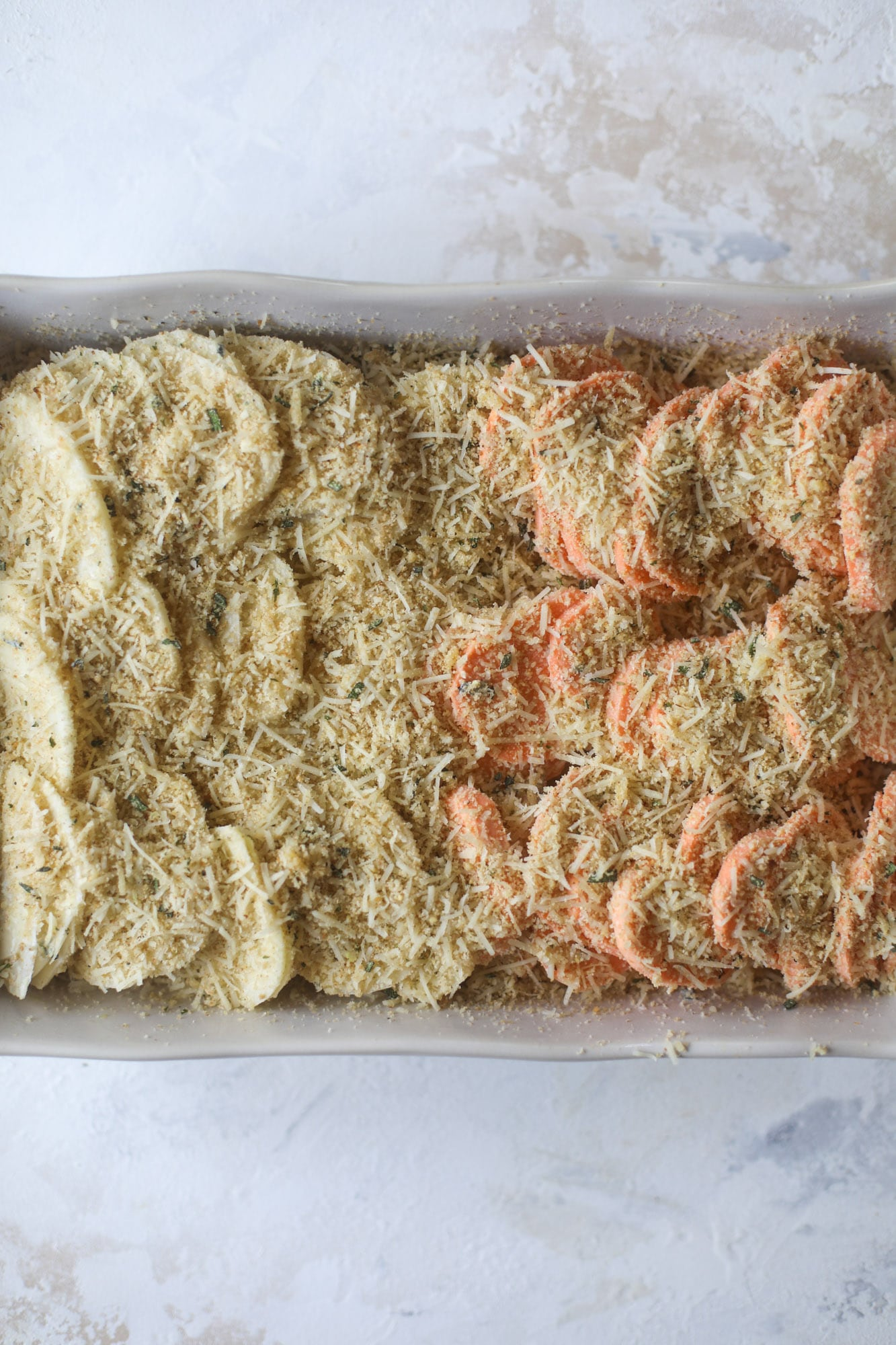These scalloped potatoes are a cheese lover's dream. Sharp asiago and cream envelops idaho and sweet potatoes in these scalloped potatoes to please everyone! The crunchy asiago topping is irresistible. I howsweeteats.com #scalloped #potatoes