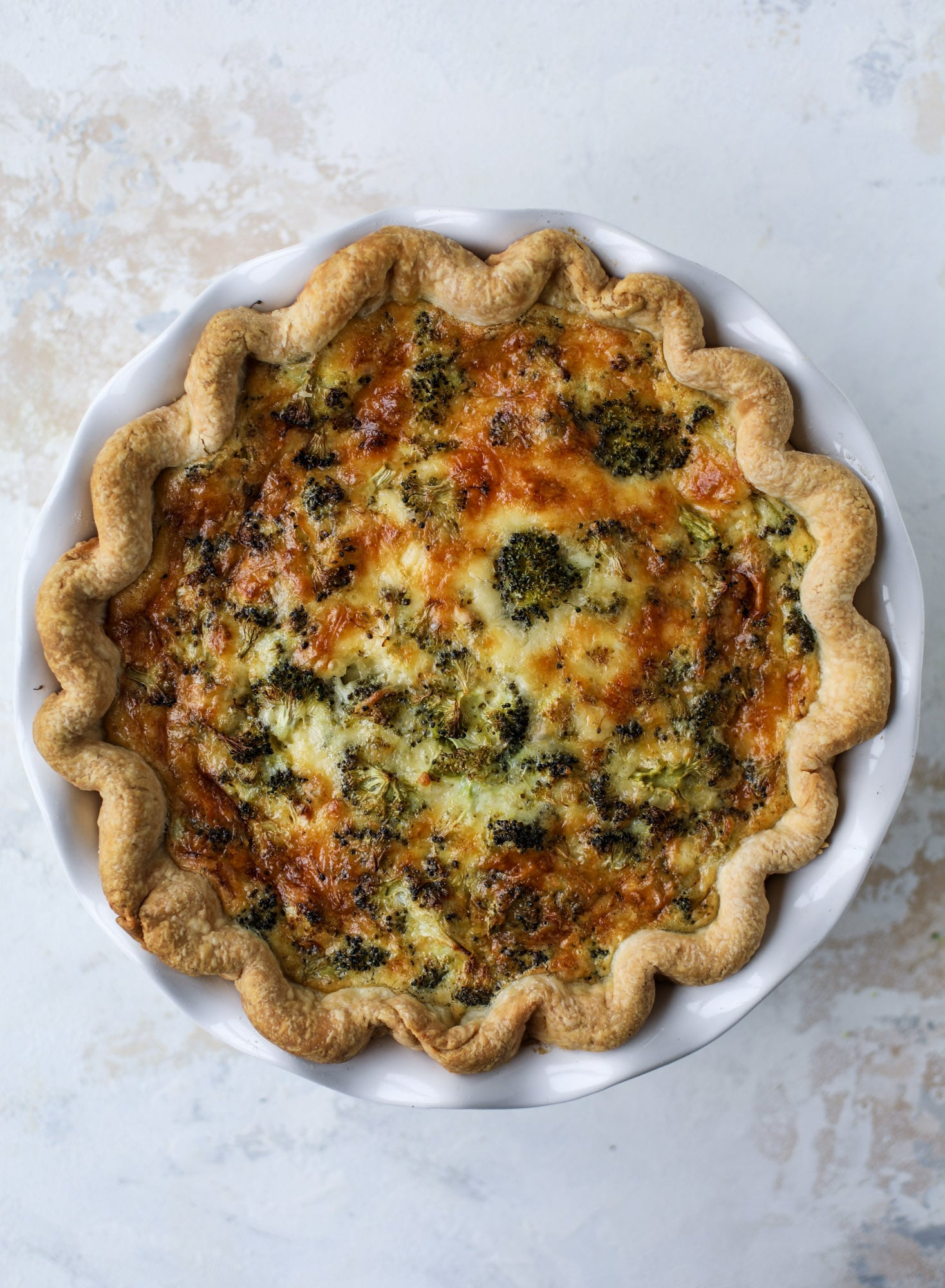 This broccoli cheese quiche is absolutely perfect for brunch, lunch or even dinner! It's delicious served warm or cold, perfect paired with a greens salad and is a recipe that can be made ahead of time! I howsweeteats.com #broccolicheese #quiche