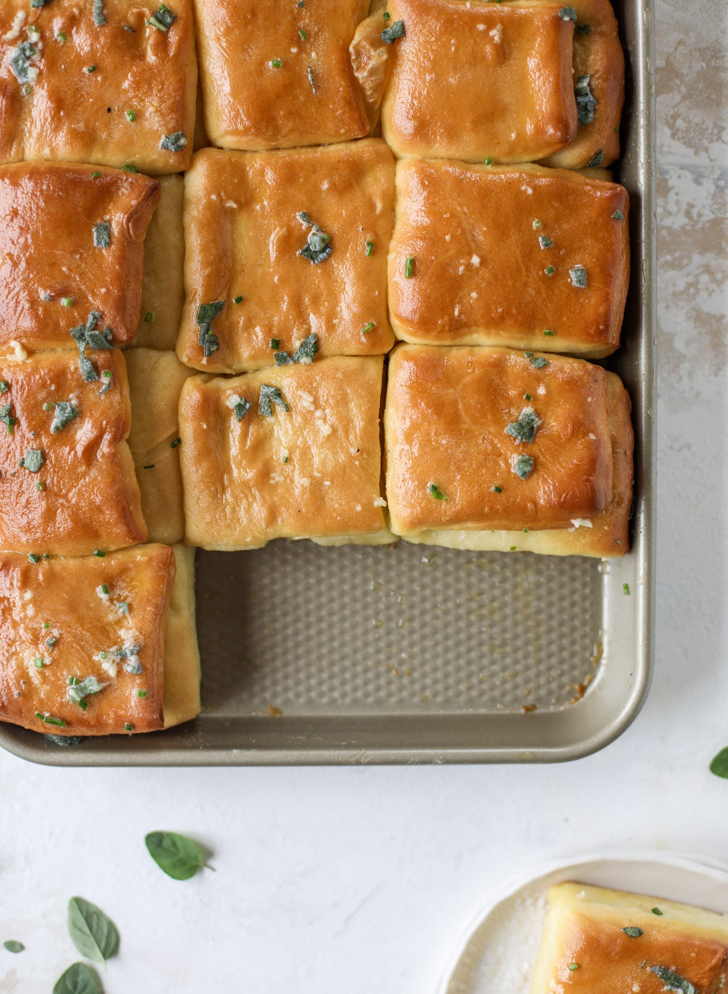 Garlic herb parker house rolls are full of incredibly buttery flavor! They are brushed with a garlic herb butter and are super fluffy, soft and tender. Perfect for Thanksgiving or the holidays and you can make the dough a bit ahead of time! I howsweeteats.com #parkerhouse #rolls