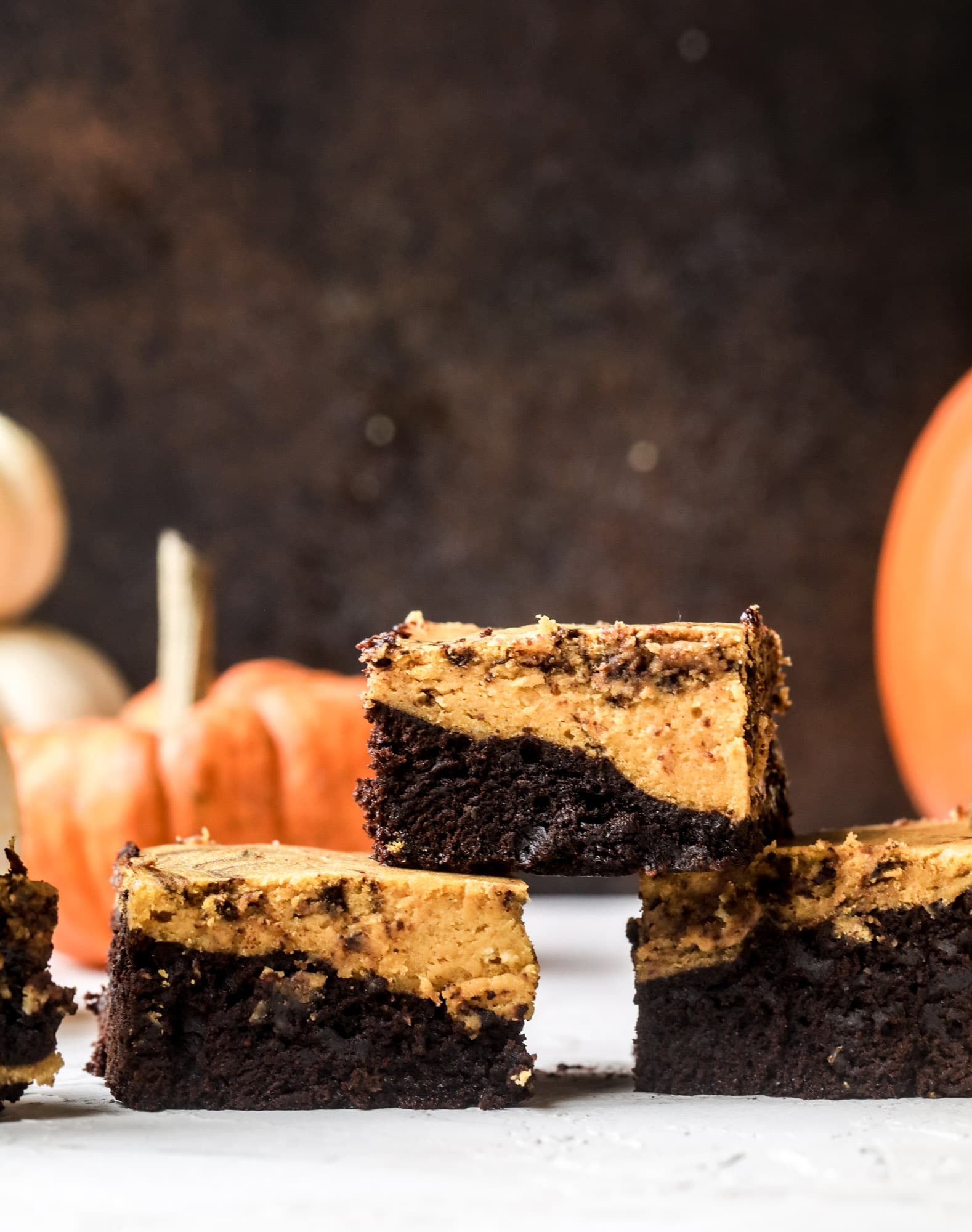 These pumpkin brownies have a fudgy layer of chocolate on the bottom and a silky layer of pumpkin on top! They are so delicious and rich and perfect for fall. The pumpkin brownies come together easily and can be made ahead of time too! I howsweeteats.com #pumpkin #brownies