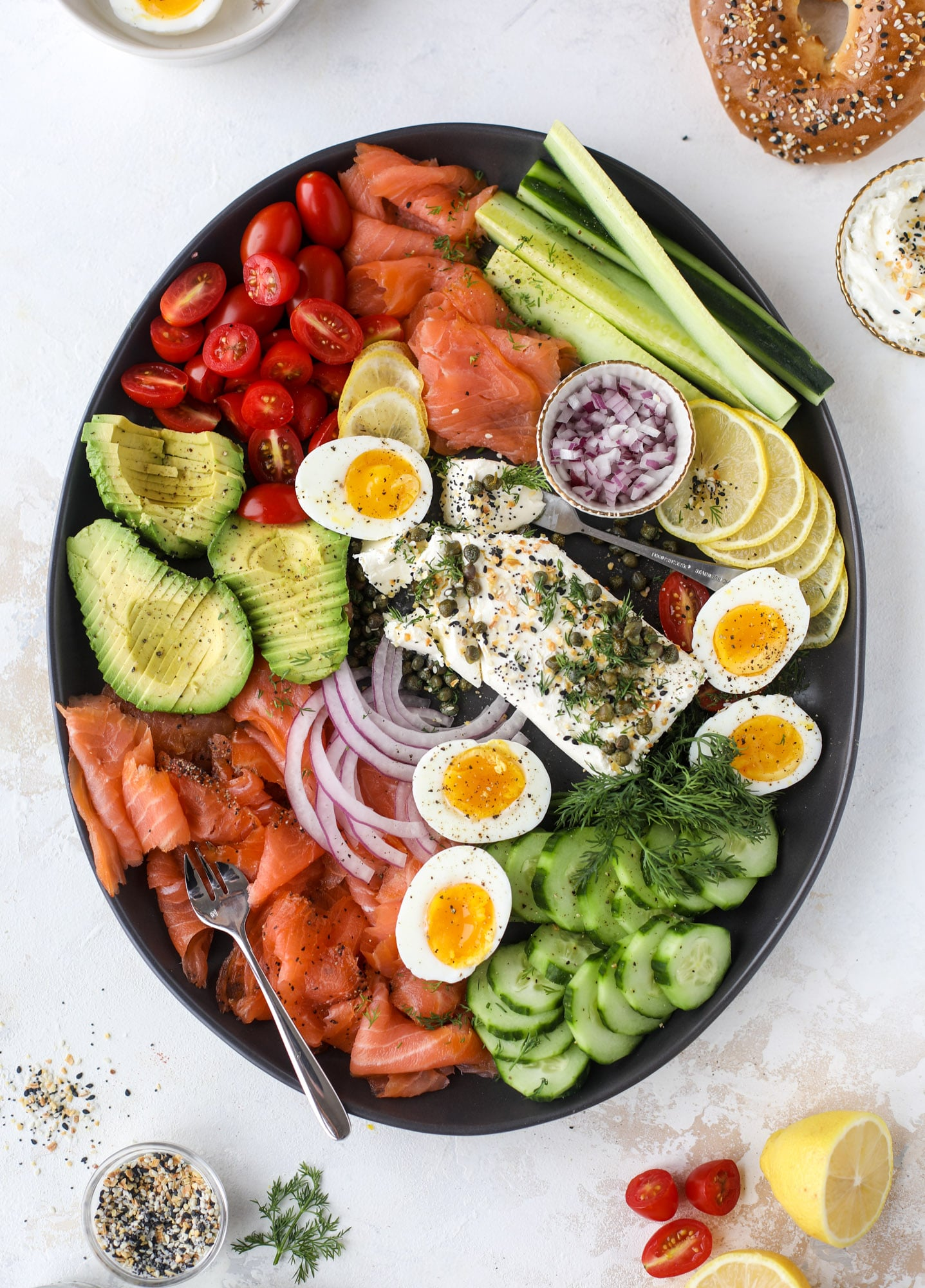 This is my favorite way to make an incredible smoked salmon platter! Fresh smoked salmon with bagels, soft boiled eggs, cream cheese and capers, everything seasoning and so much more. Perfect for holiday breakfasts and brunches! I howsweeteats.com #smokedsalmon #platter