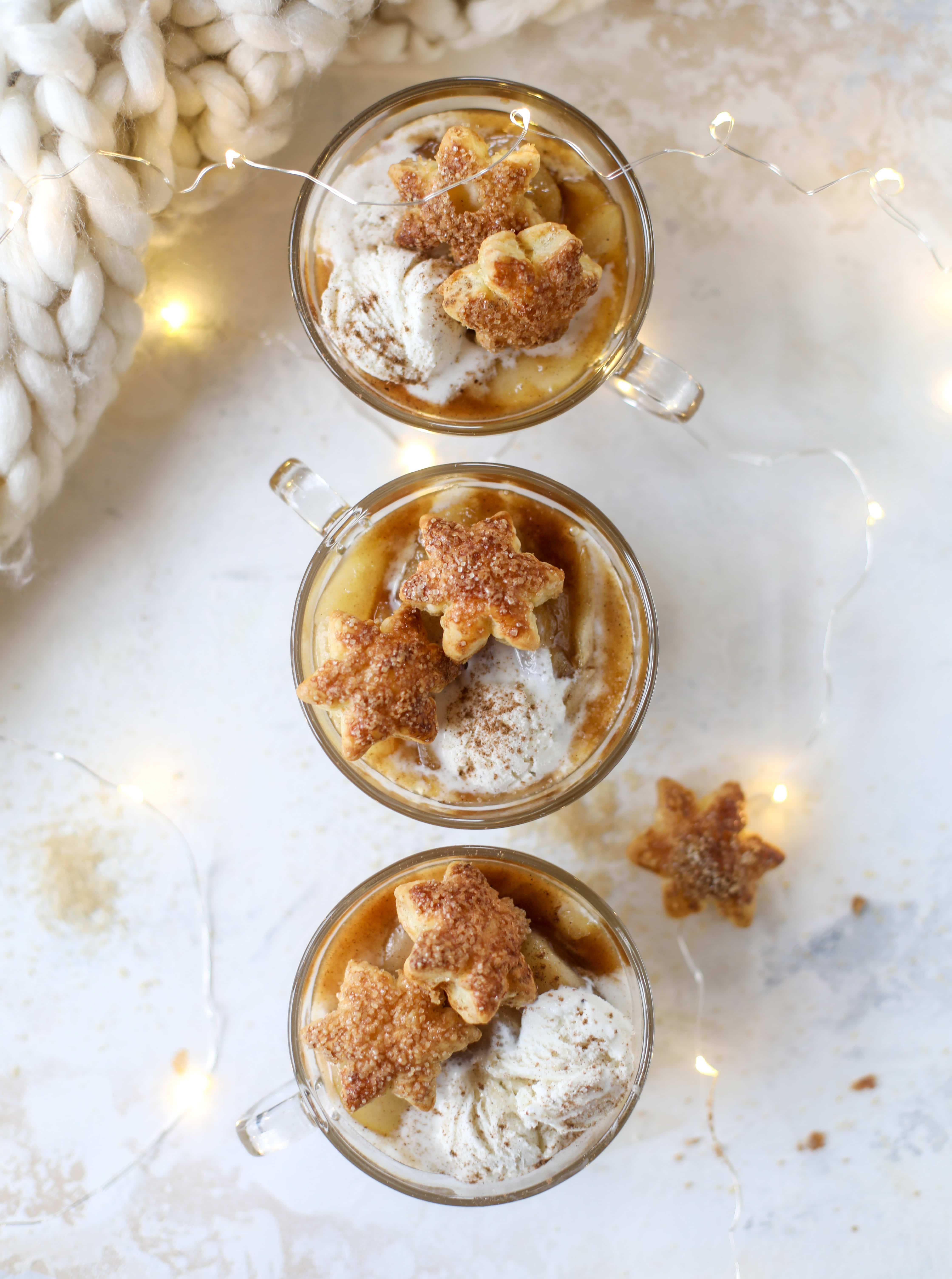 This pear mug pie is the coziest way to enjoy warm, caramelized pears. Topped with vanilla ice cream and the cutest, quick puff pastry stars, these are a great dessert for a dinner party or an easy one to make for yourself on a Saturday night! I howsweeteats.com #pear #mugpie
