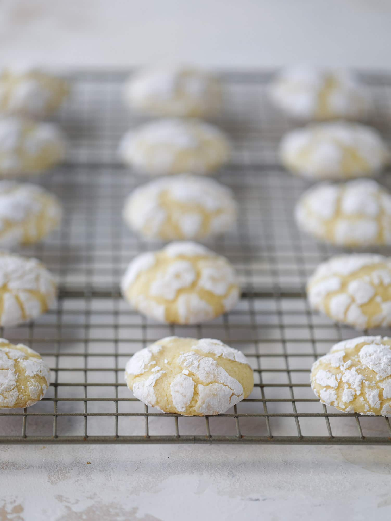 These lemon crinkle cookies are perfect if you love lemon desserts! They take after chocolate crinkle cookies, but are a delightful refreshing lemon flavor sprinkle with powdered sugar. These are always a huge hit! I howsweeteats.com #lemoncrinkle #cookies