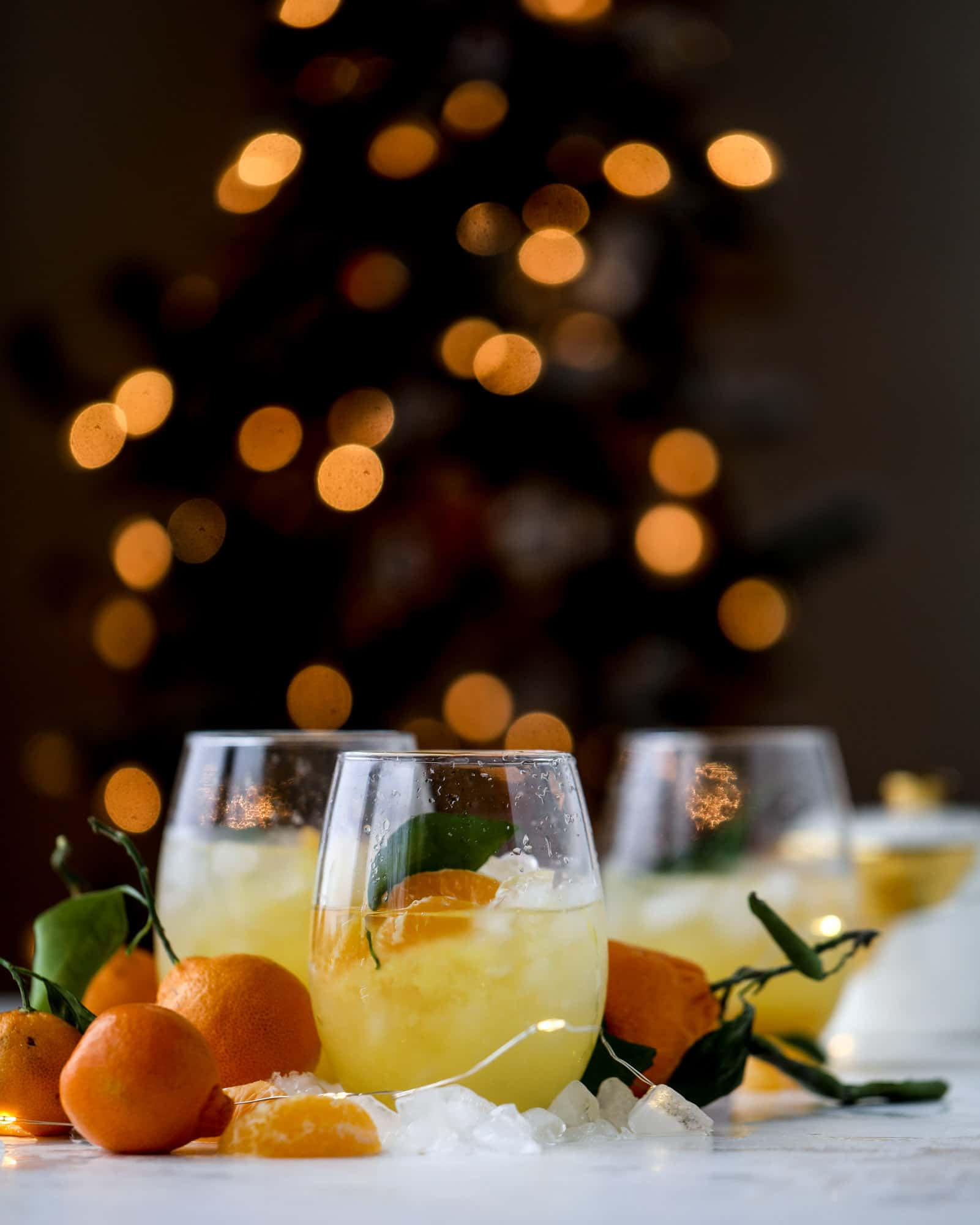 This satsuma cocktail is perfect for the holiday season and winter months when sweet satsumas are in season! This cocktail uses gin or vodka and is topped with champagne and garnished with a few satsuma wedges. Delicious! I howsweeteats.com #satsuma #cocktail