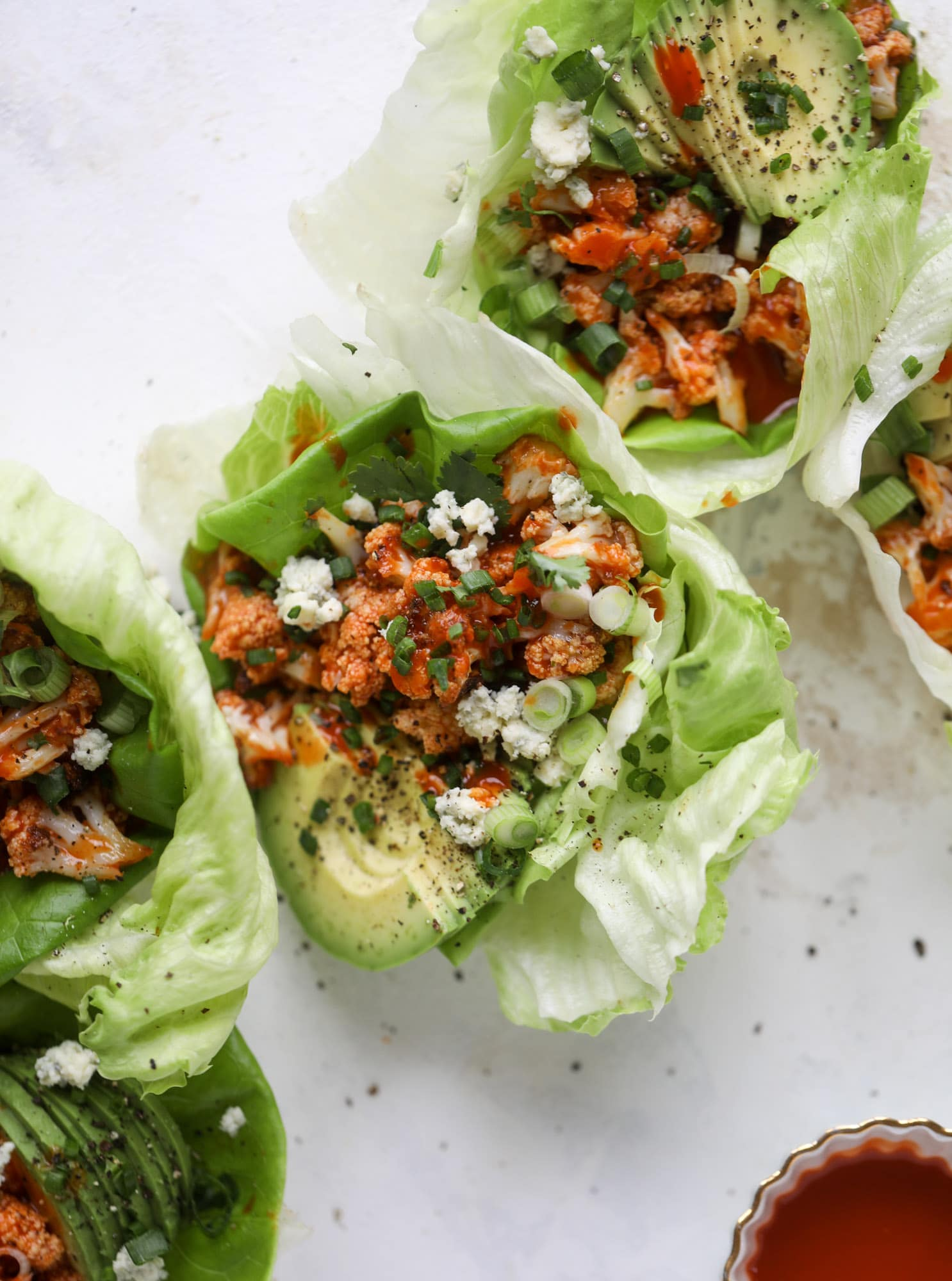 These buffalo cauliflower lettuce wraps are perfect for game day or even a quick weeknight dinner. Roasted cauliflower with buffalo wing sauce, sliced avocado, crumbled blue cheese, scallions, cilantro and chives makes for a flavor explosion! I howsweeteats.com #buffalo #cauliflower