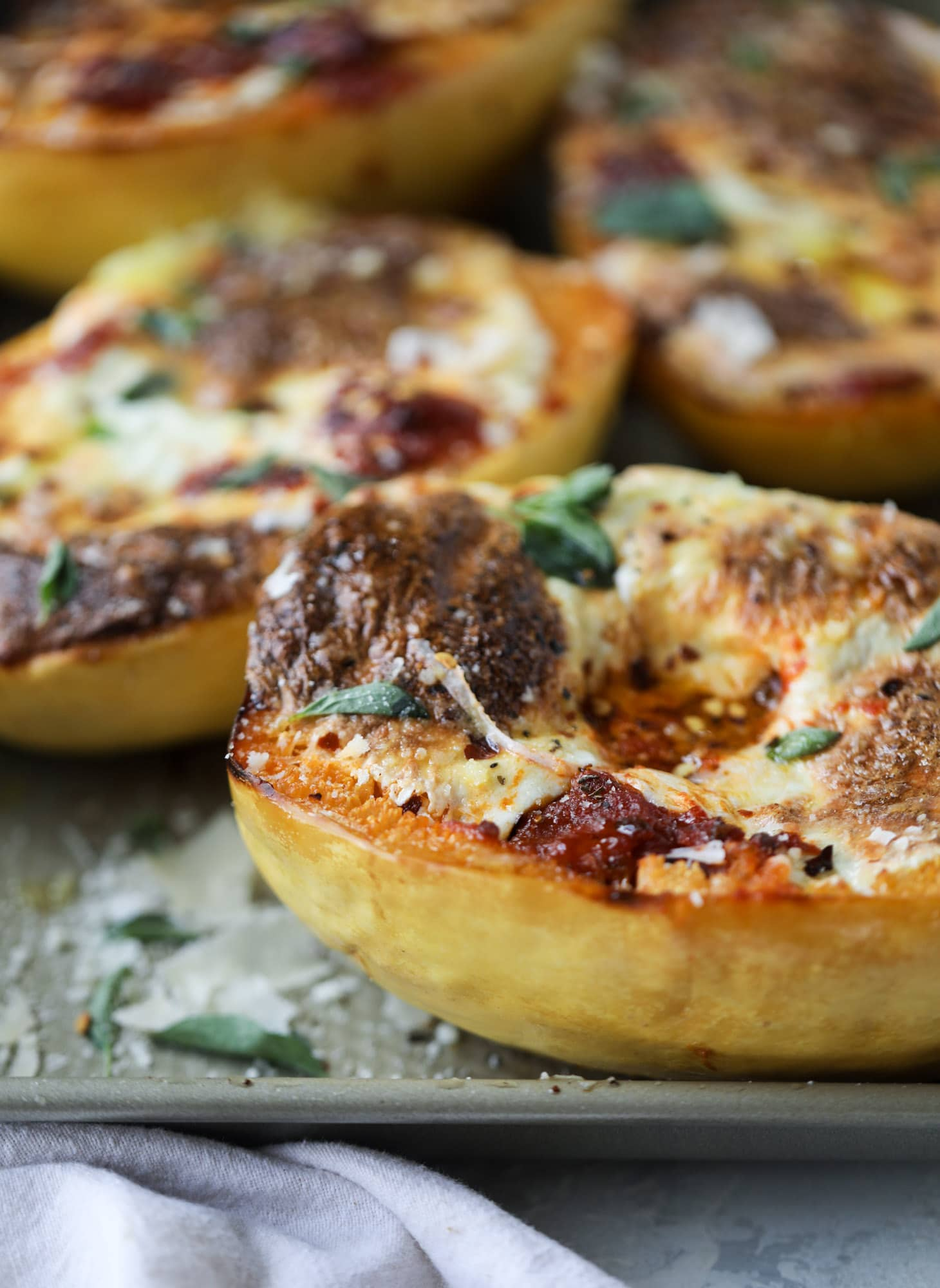Spaghetti squash parmesan is a delicious weeknight meal! Topped with marinara or bolognese, melty cheese and fresh herbs, it's easy and delicious! I howsweeteats.com #spaghettisquash #parmesan