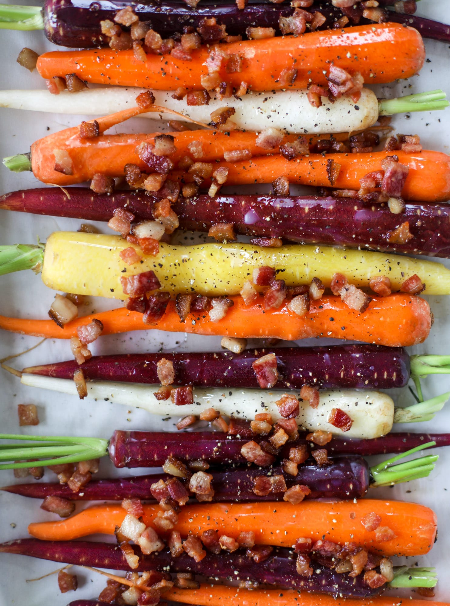 Sweet carrots are drizzled with bacon fat and chopped bacon, then roasted until they are tender, sweet and caramely. So much flavor!