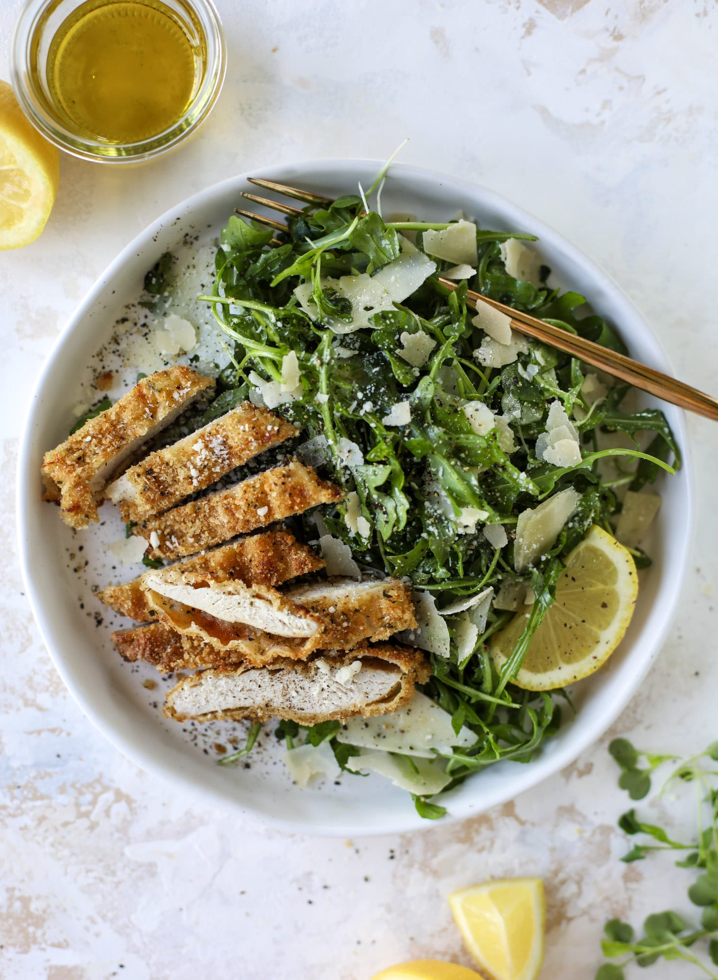Crispy baked parmesan chicken is so super easy and delicious! It's an amazing weeknight meal served with a lemon arugula salad. Delish!
