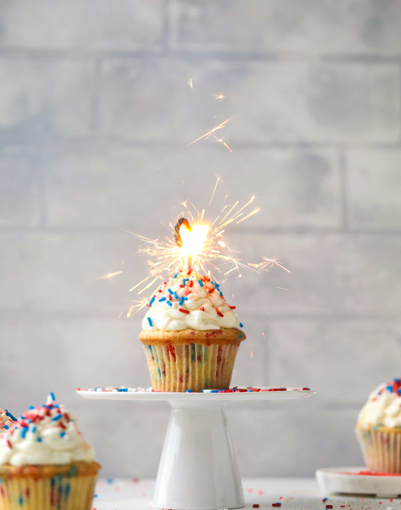 These 4th of July confetti cupcakes are super fun! Firecracker cupcakes with red, white and blue sprinkles and pop rocks candy on top for crackle!