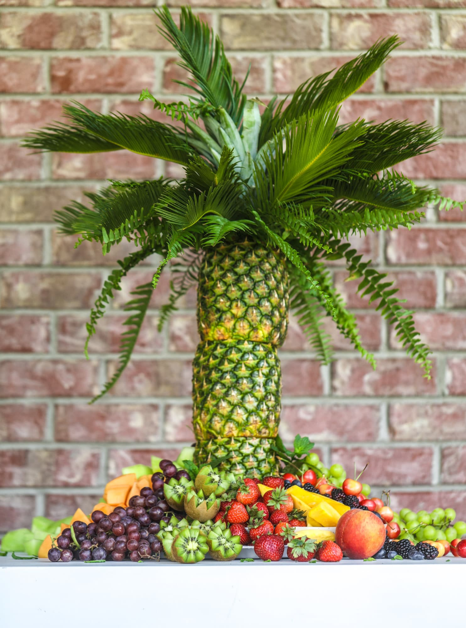 This is the cutest way to display fruit! A pineapple palm tree fruit tray will be the star of the show at your next summer BBQ or party!