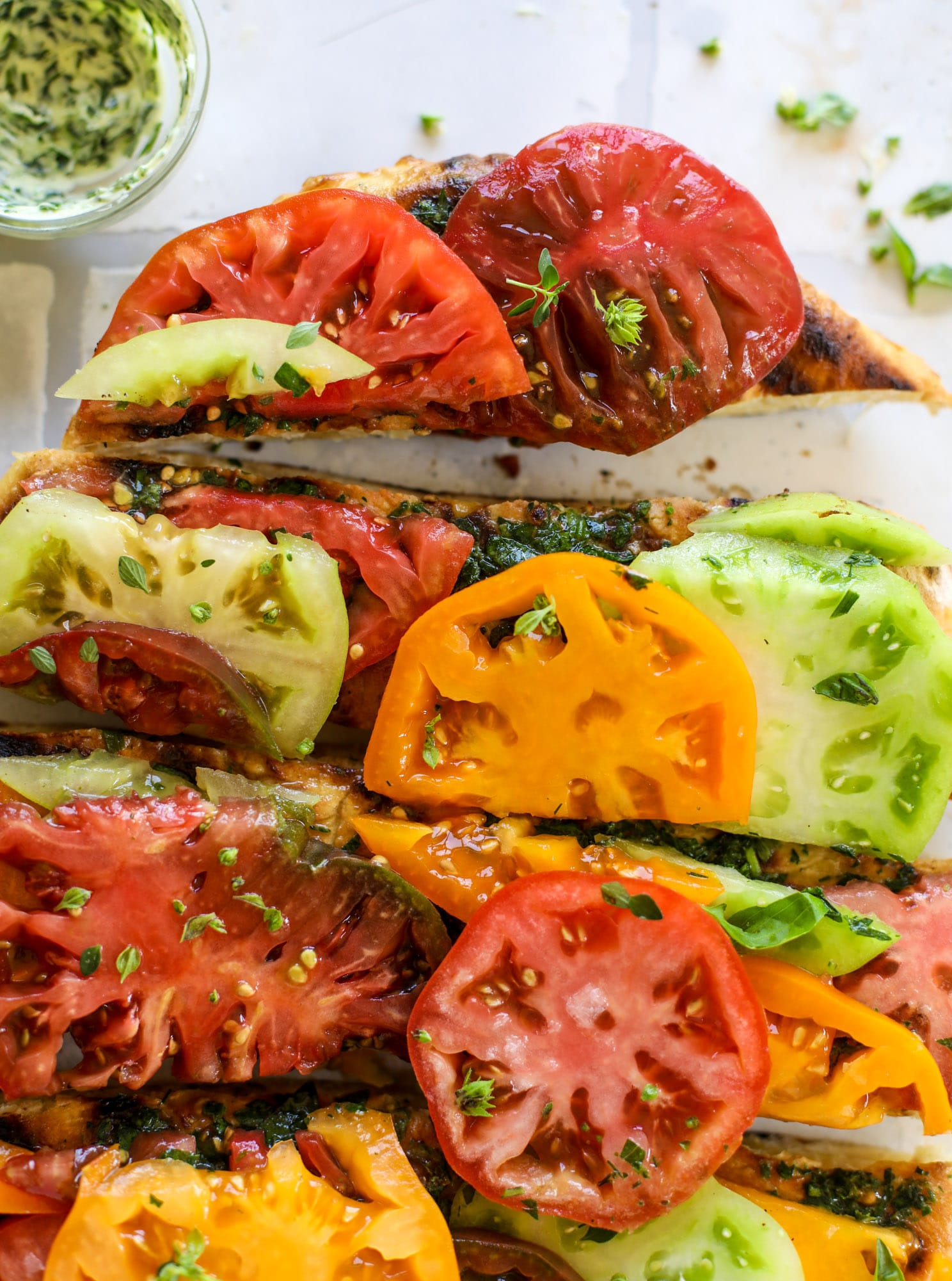 This heirloom tomato pizza starts with a grilled garlic herb butter crust! Melty herb butter and sliced fresh tomatoes top it off for a delicious bite!