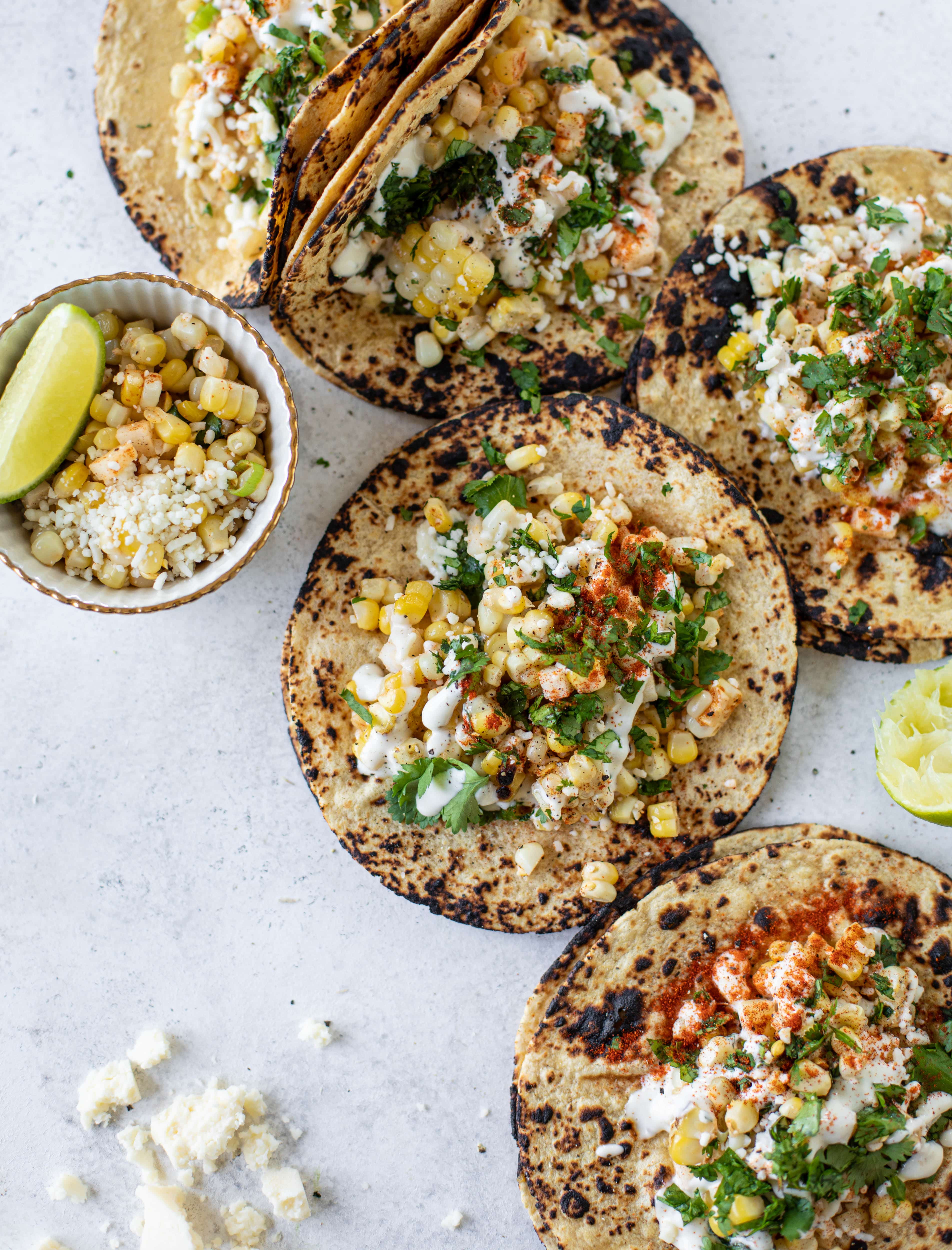 These street corn tacos are filled with a jicama corn salad and drizzled with garlic mayo. This little taco packs a major flavor punch.