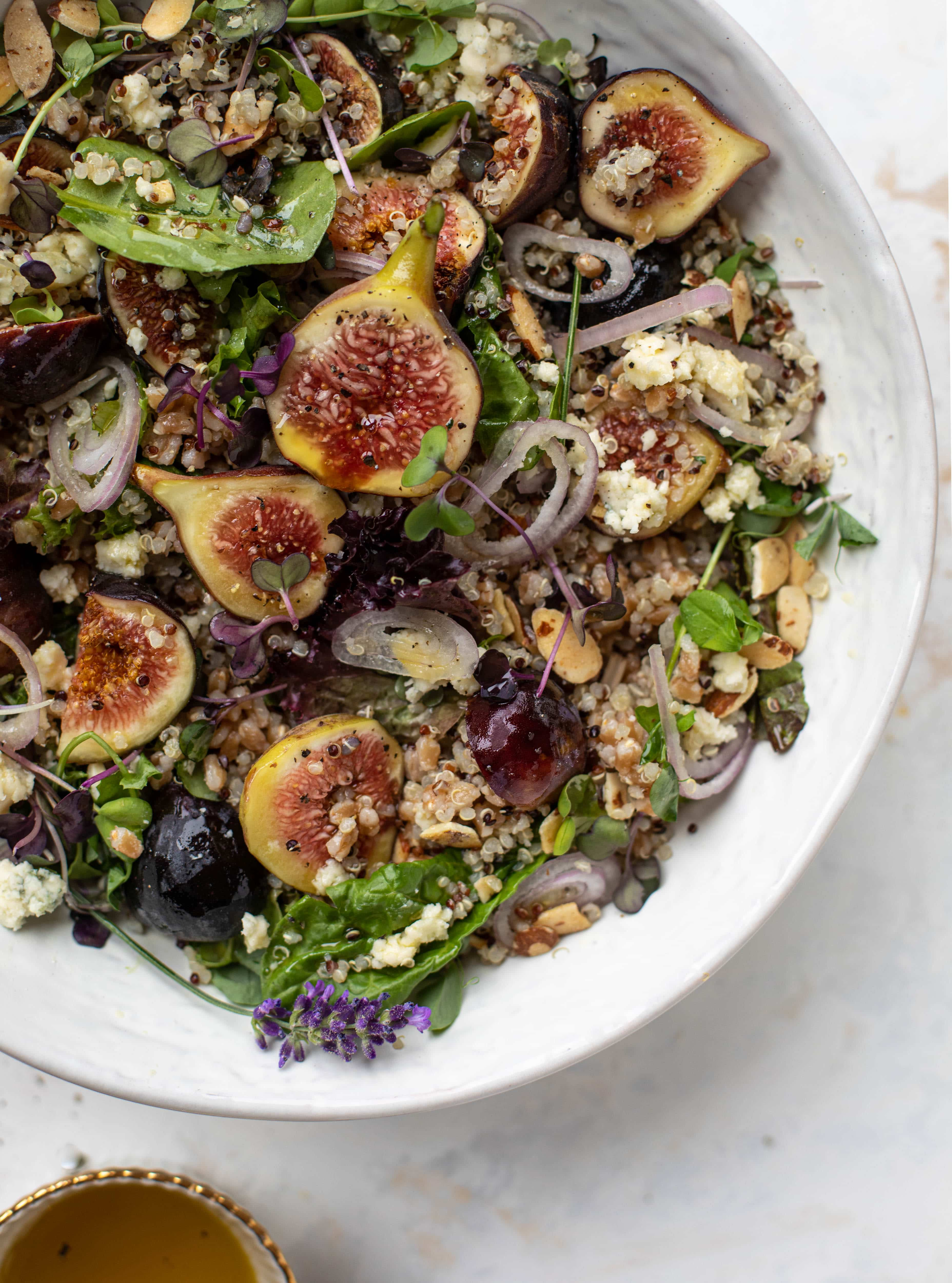These grain bowls are the perfect September salad! Juicy figs, greens, quinoa, farro, almonds and a lemon lavender vinaigrette make this bowl irresistible.