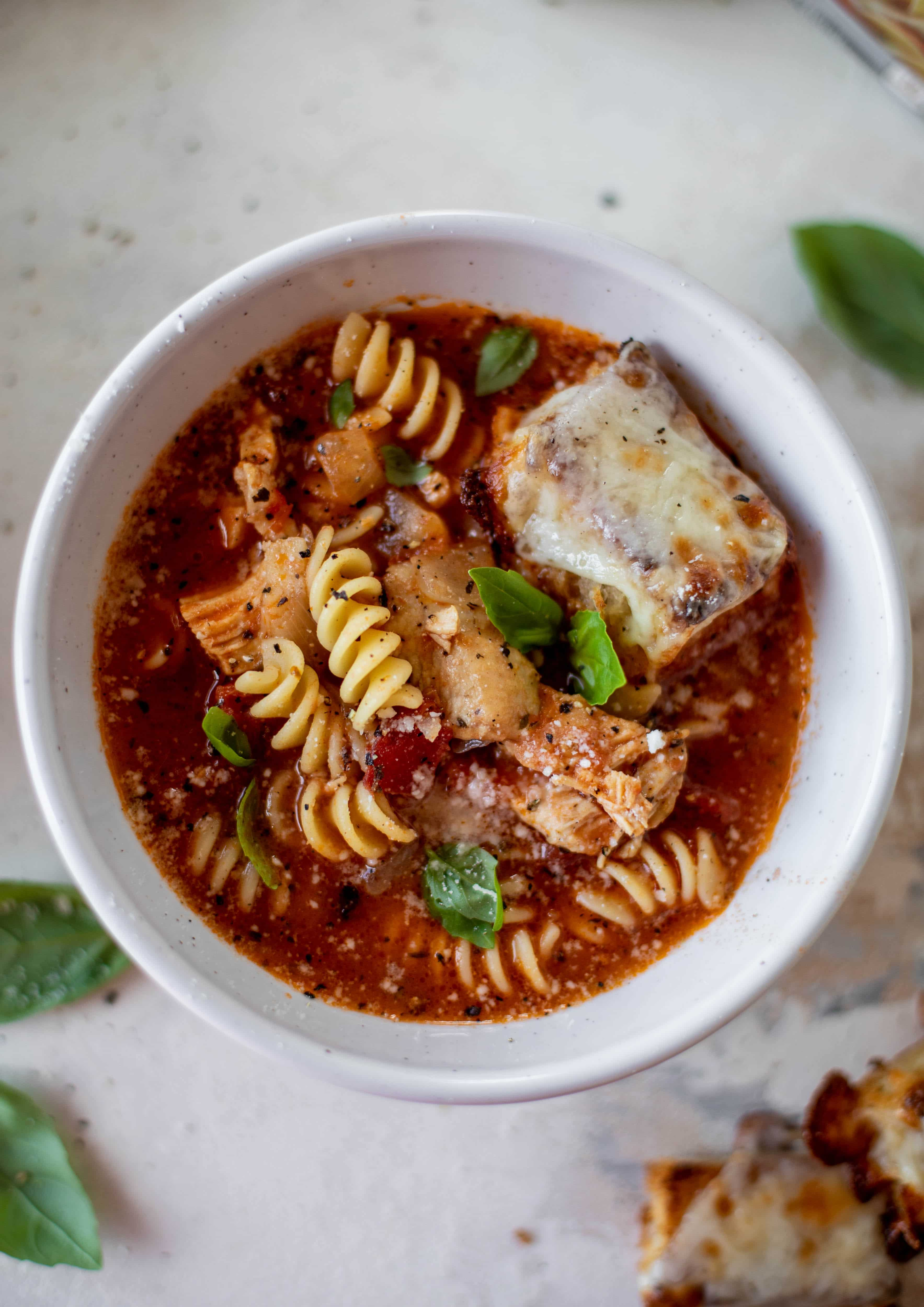 This chicken parmesan soup is ridiculously flavorful and so easy to make! Juicy chicken with pasta, fire roasted tomatoes and mozzarella croutons. Yum!