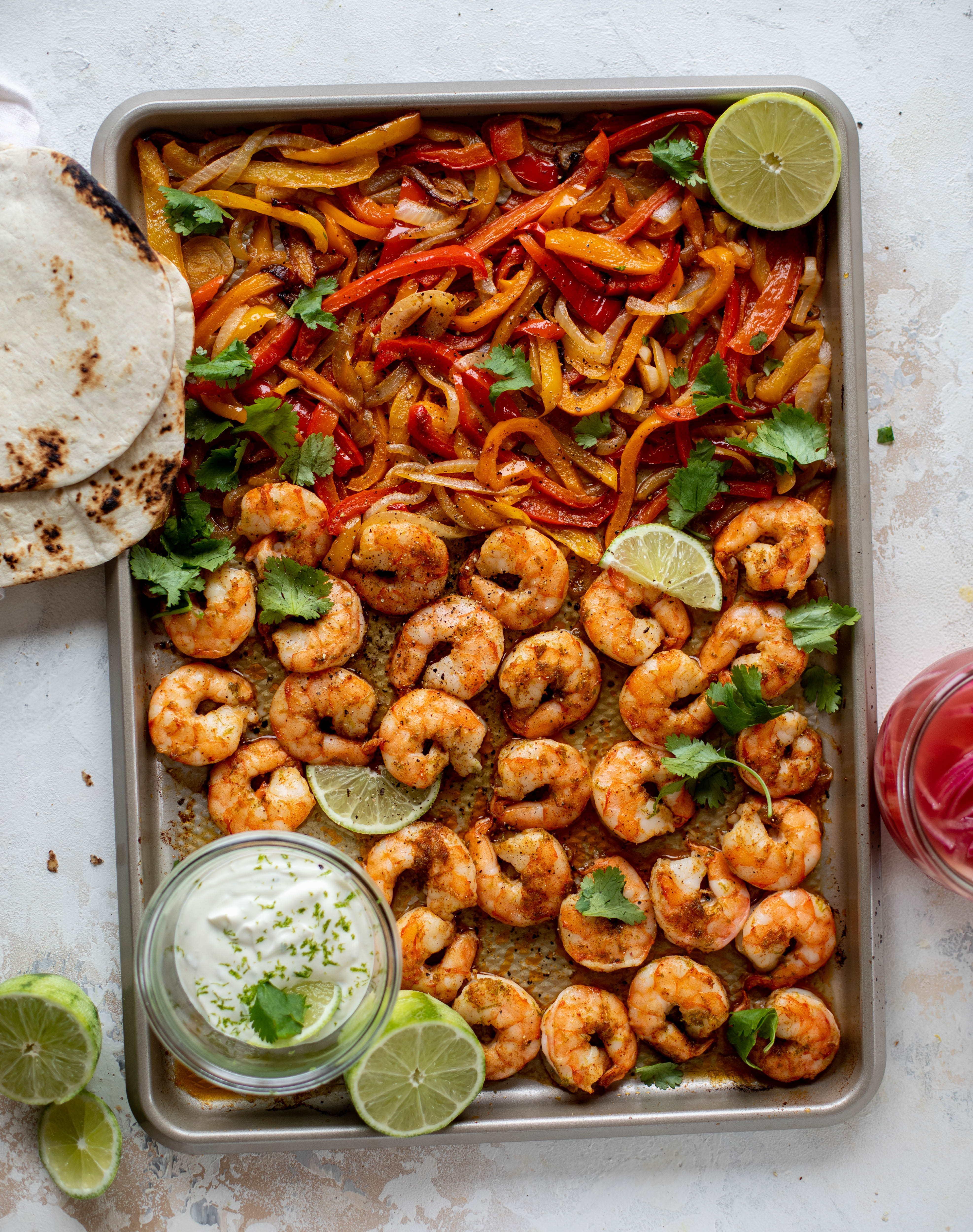 These lime sheet pan shrimp fajitas are the best weeknight meal! Make everything on the sheet pan and serve in warm tortillas. Delicious!