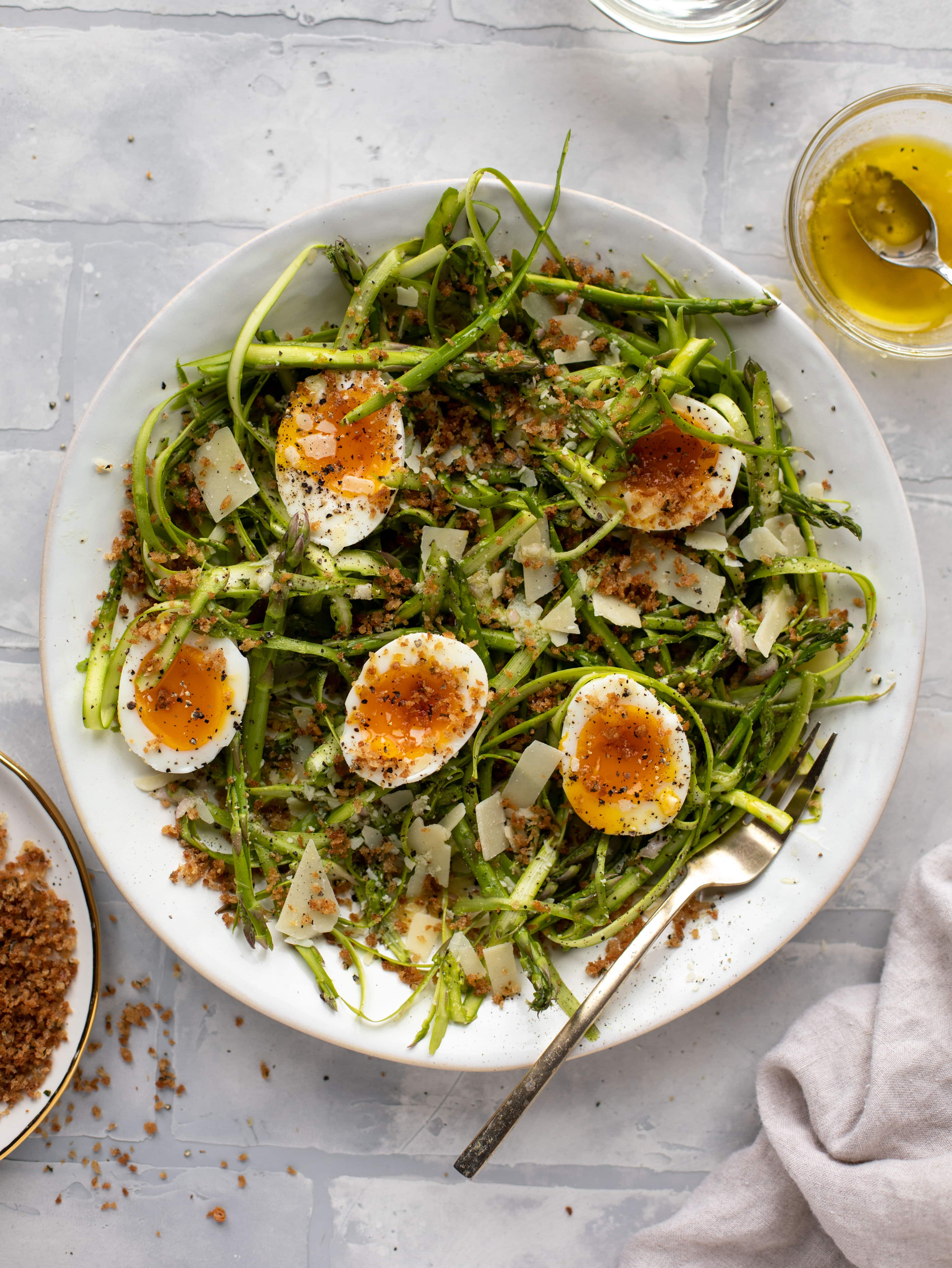 This shaved asparagus salad is tossed with a delicious parmesan vinaigrette, then topped with soft boiled eggs and finished with crunchy garlic breadcrumbs!