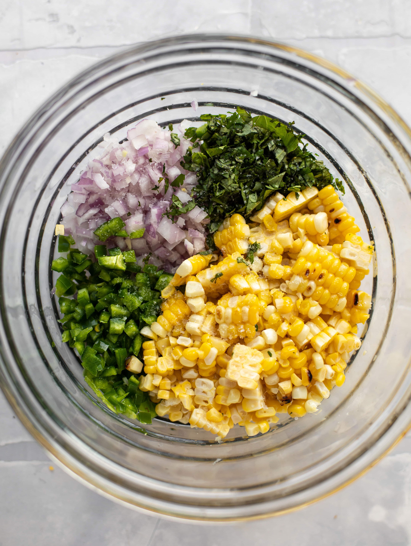 corn, jalapeno, onion, cilantro and basil in a bowl
