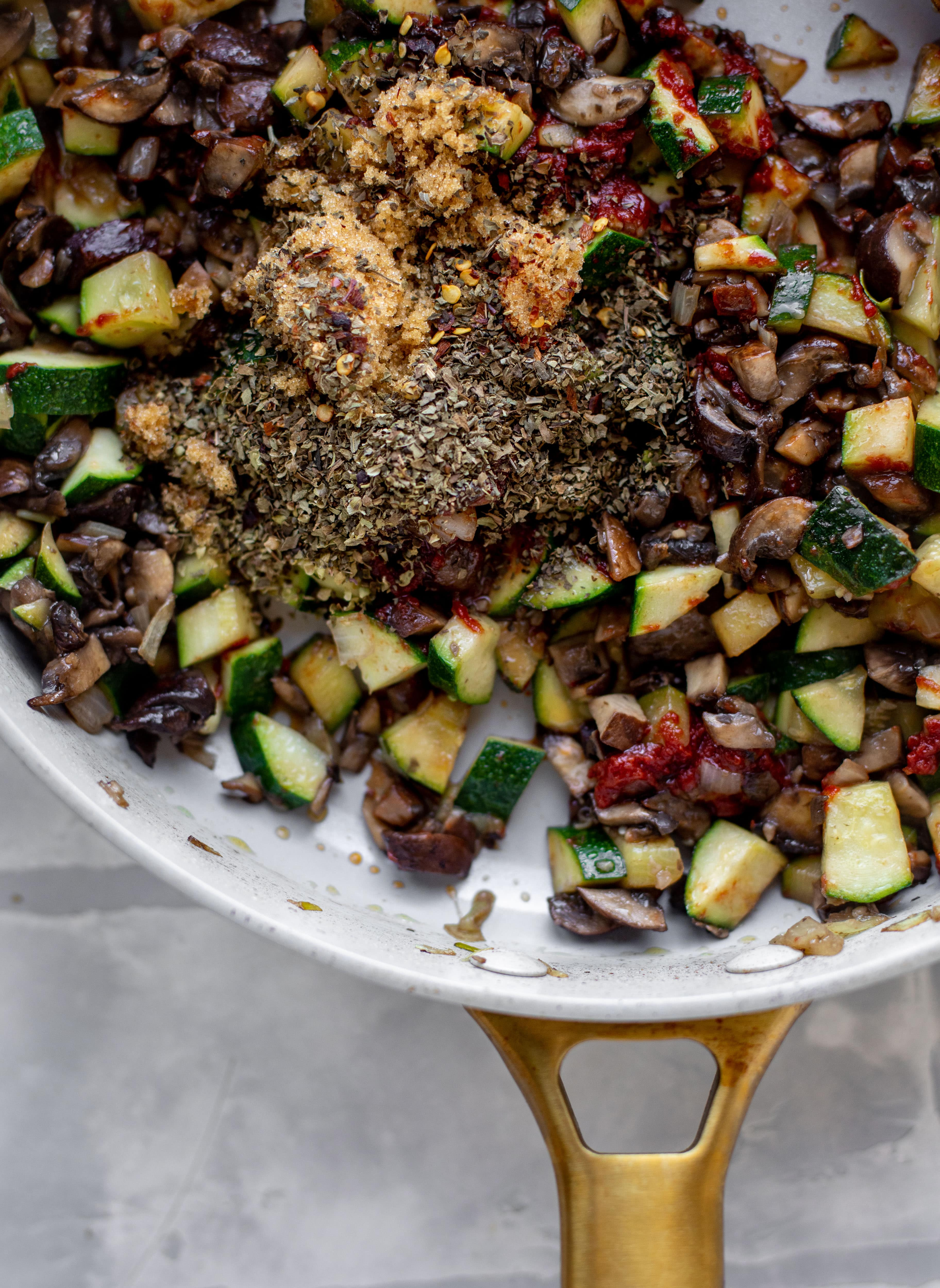 spices with zucchini and mushrooms in a skillet
