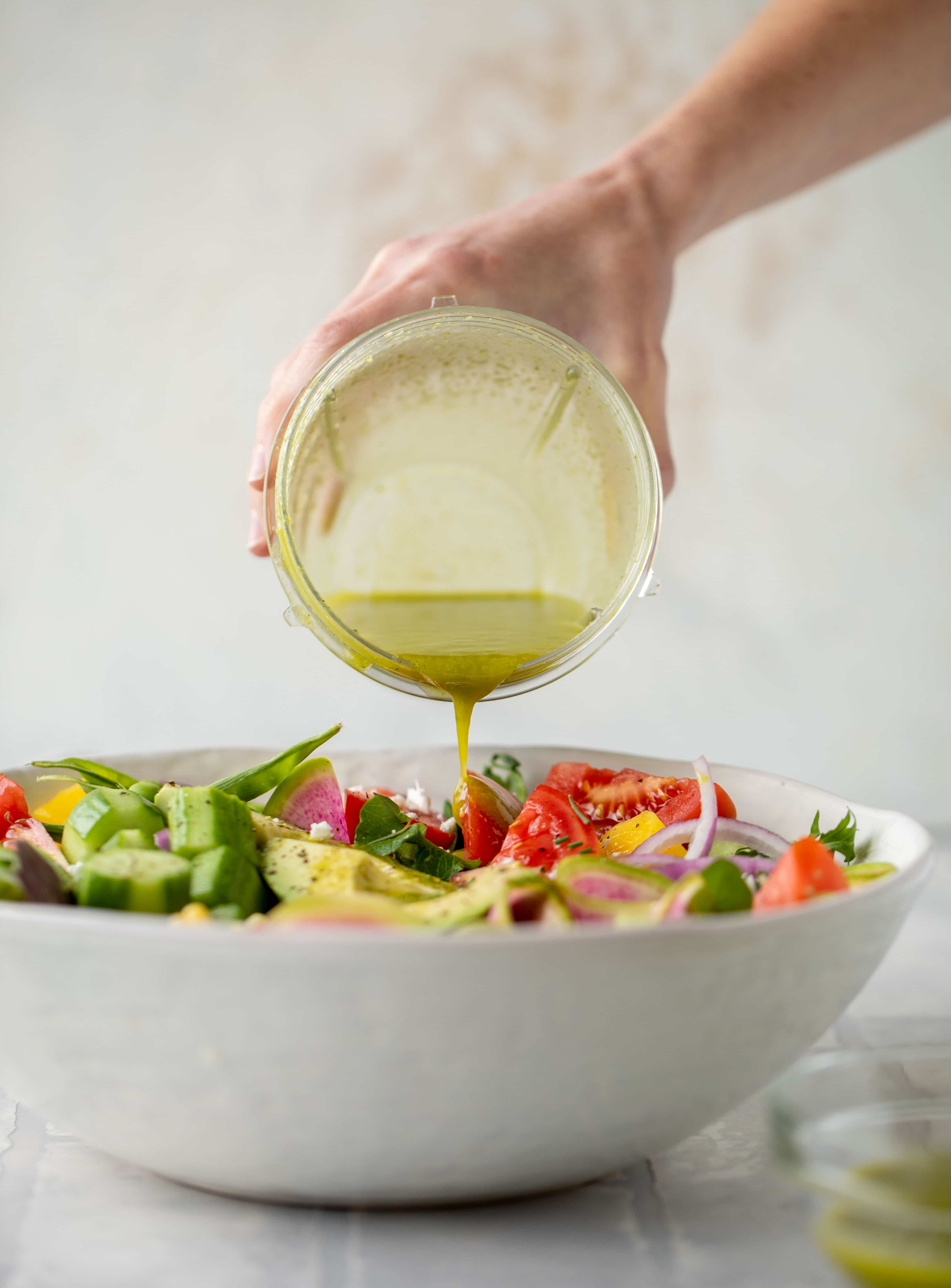 pouring vinaigrette on salad