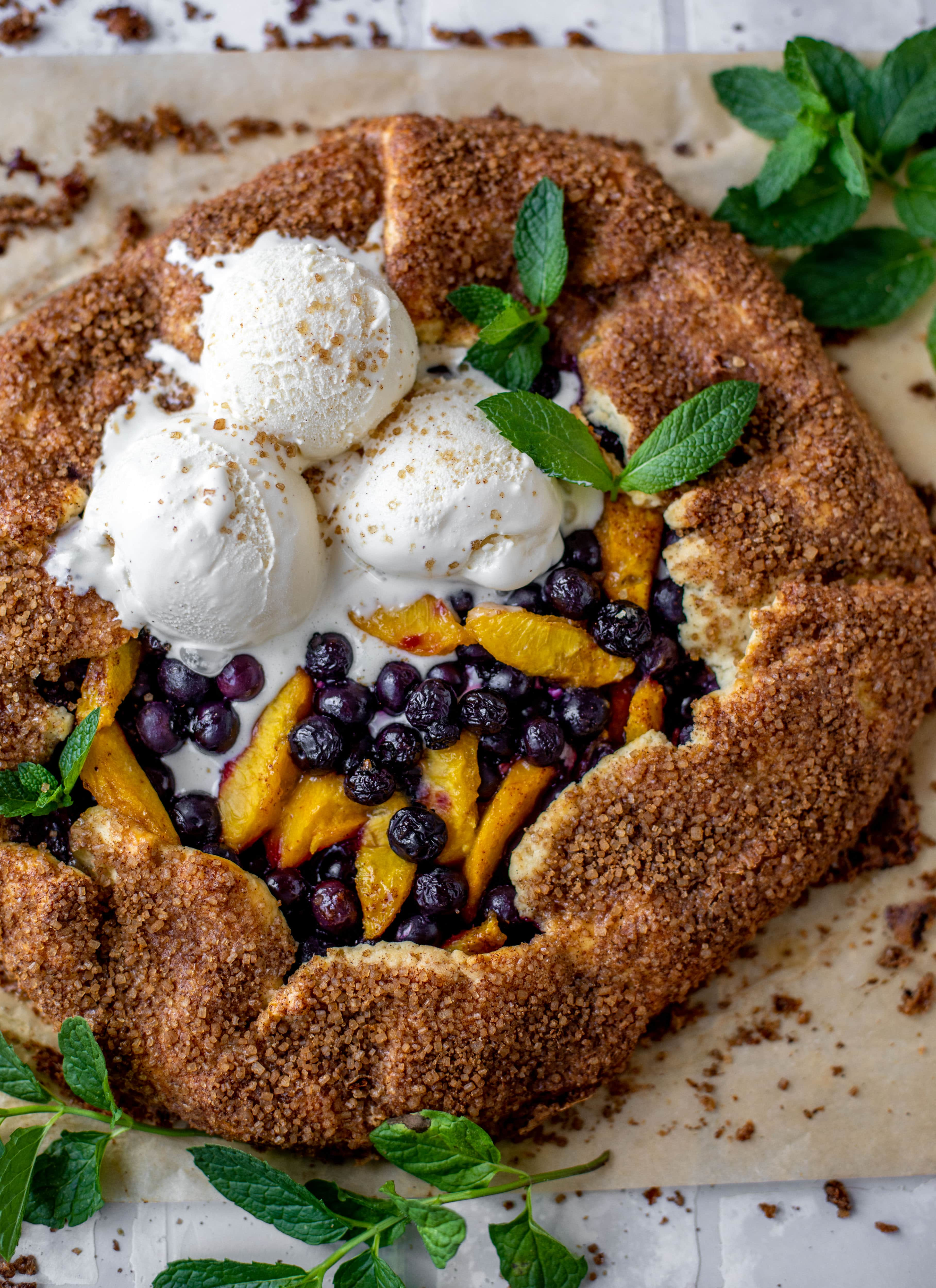 blueberry peach galette with cinnamon sugar galette topped with ice cream and fresh mint