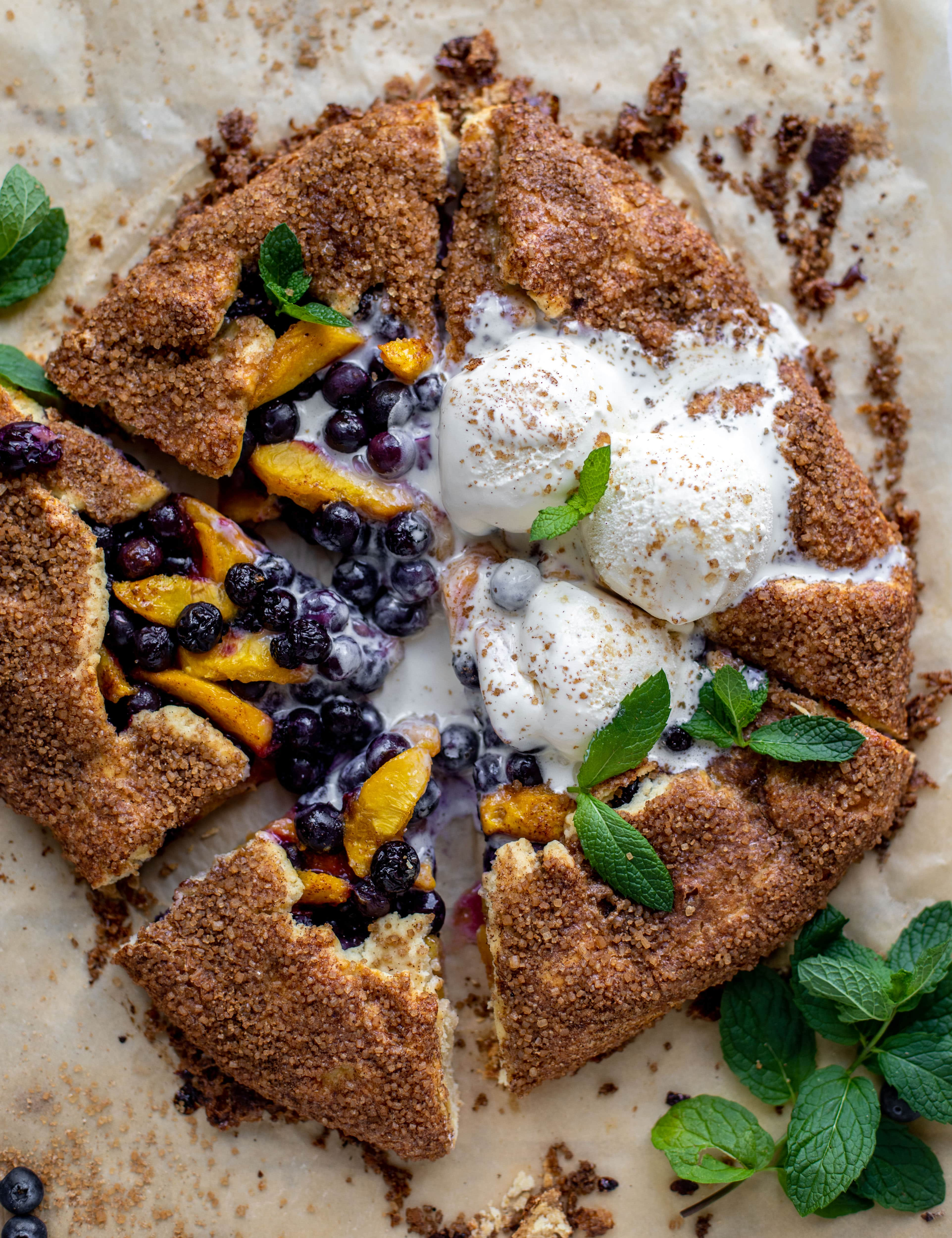 sliced blueberry peach galette with cinnamon sugar galette topped with ice cream and fresh mint