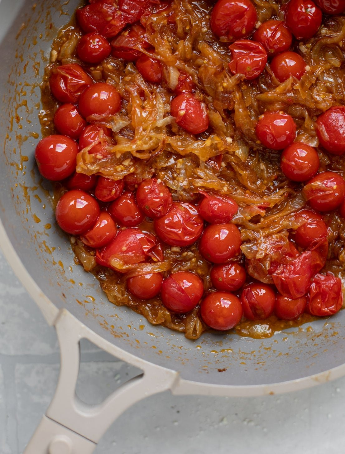 caramelized onions and burst cherry tomatoes in a skillet