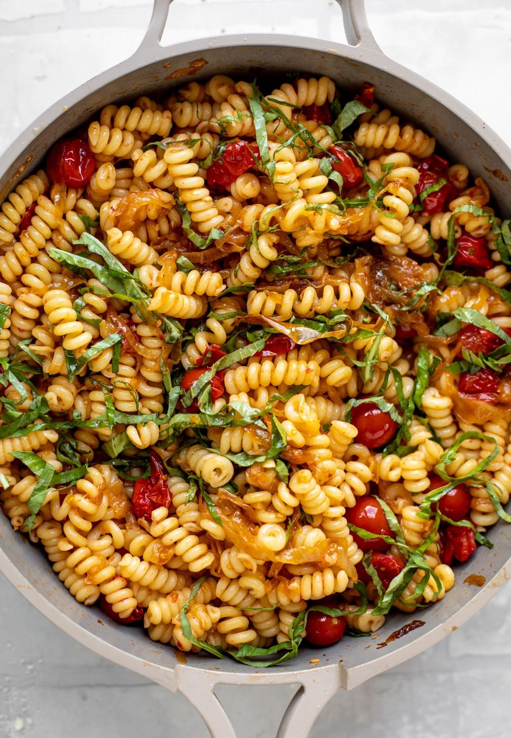 caramelized onion tomato pasta with basil in a skillet