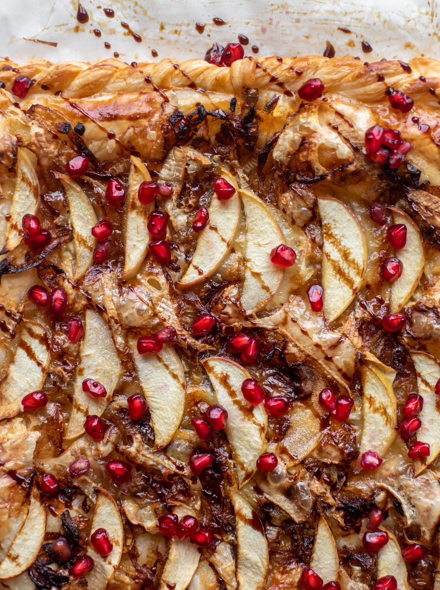 This apple brie tart starts with caramelized onions and puff pastry. It's topped with pomegranate molasses and juicy arils for an extra pop!