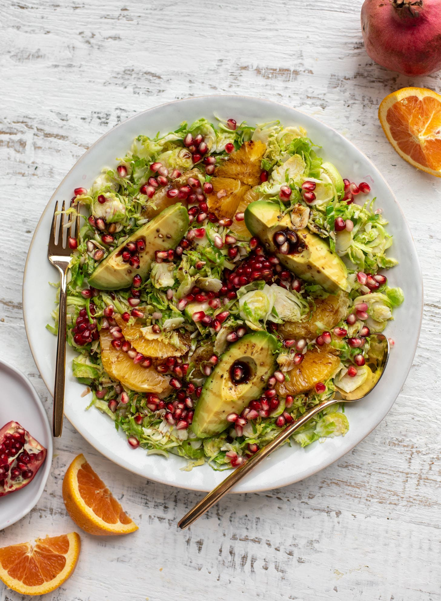 shredded citrus brussels sprouts salad with avocado and pomegranate