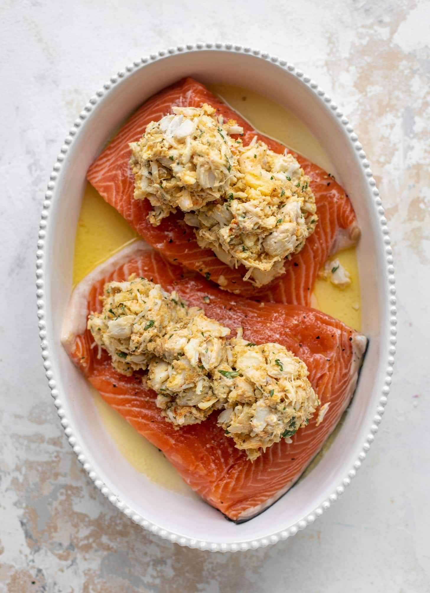 salmon in a baking dish topped with crabmeat
