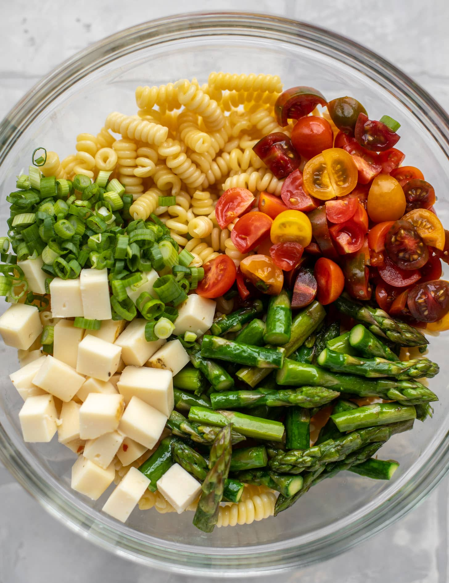 pasta, scallions, tomatoes, asparagus, cheddar in a bowl