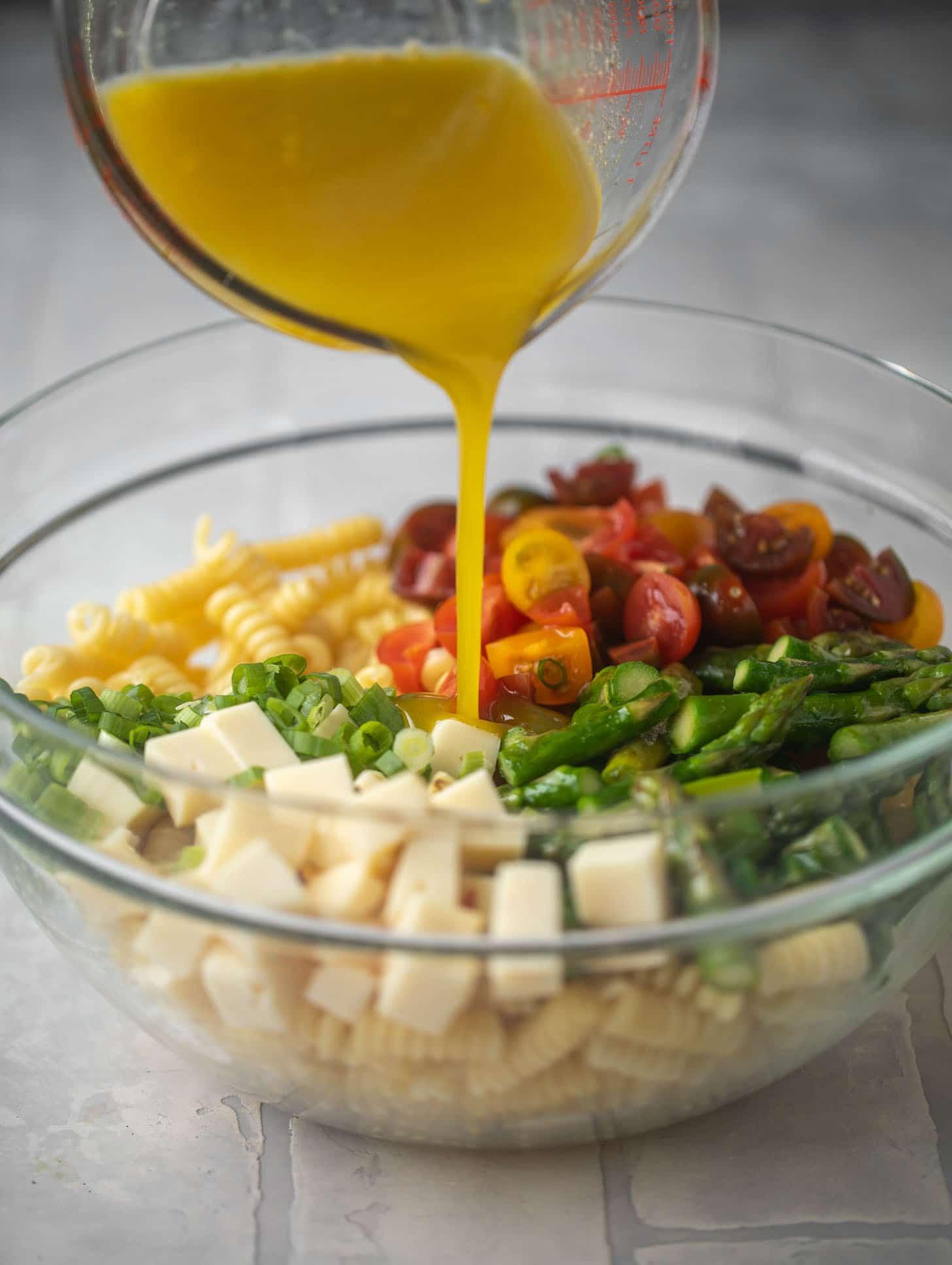 pouring honey mustard dressing on asparagus pasta salad