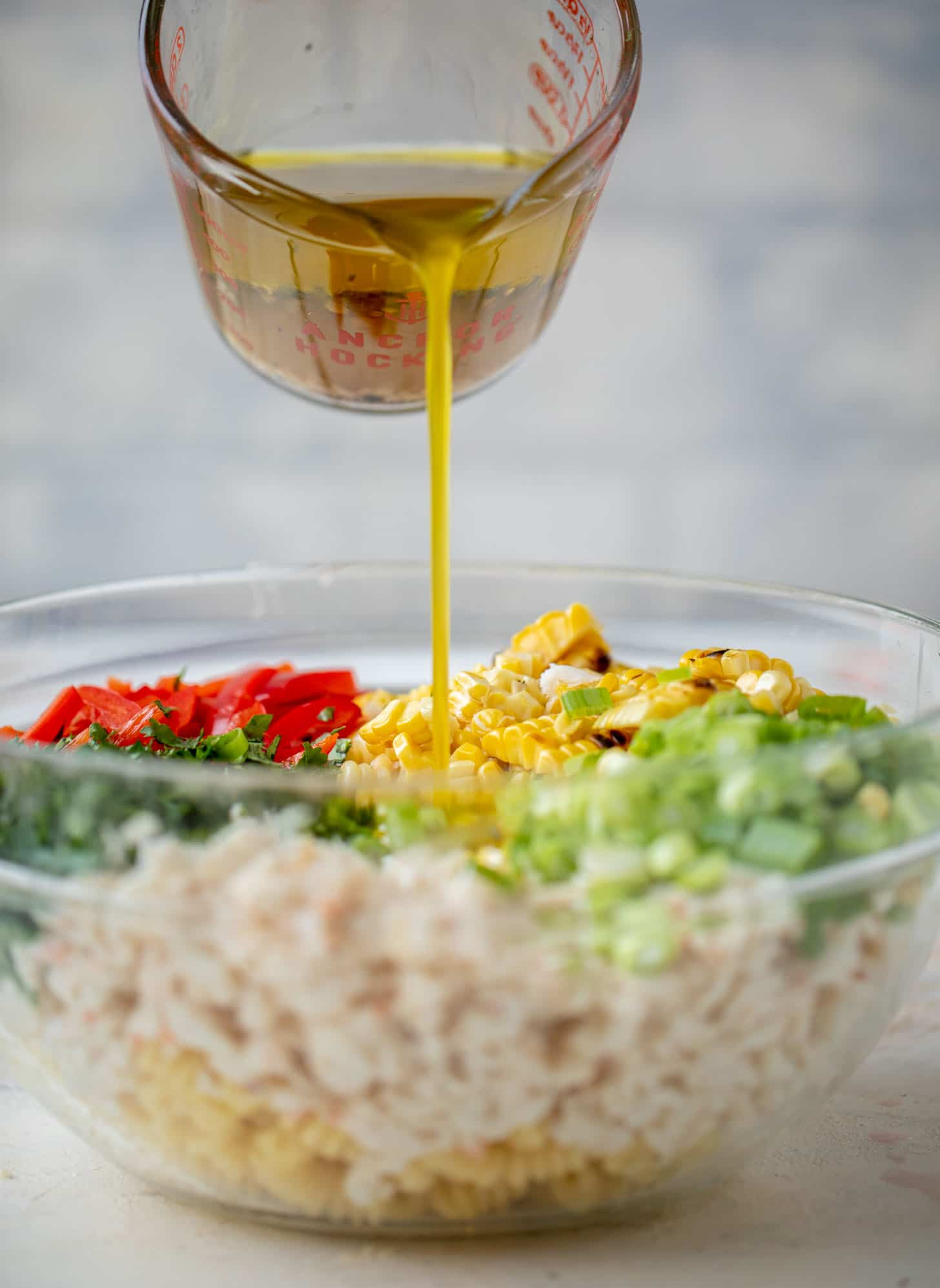 pouring dressing on grilled corn and crab pasta salad