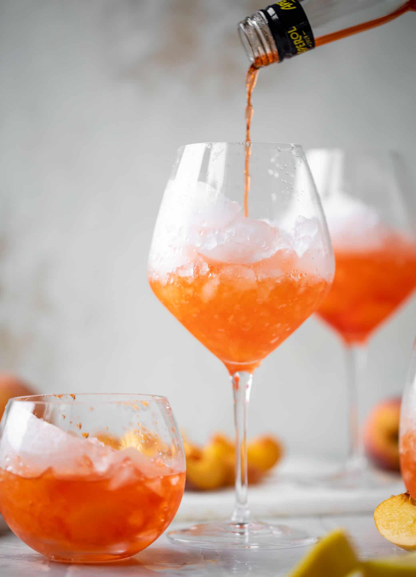 pouring aperol over crushed ice