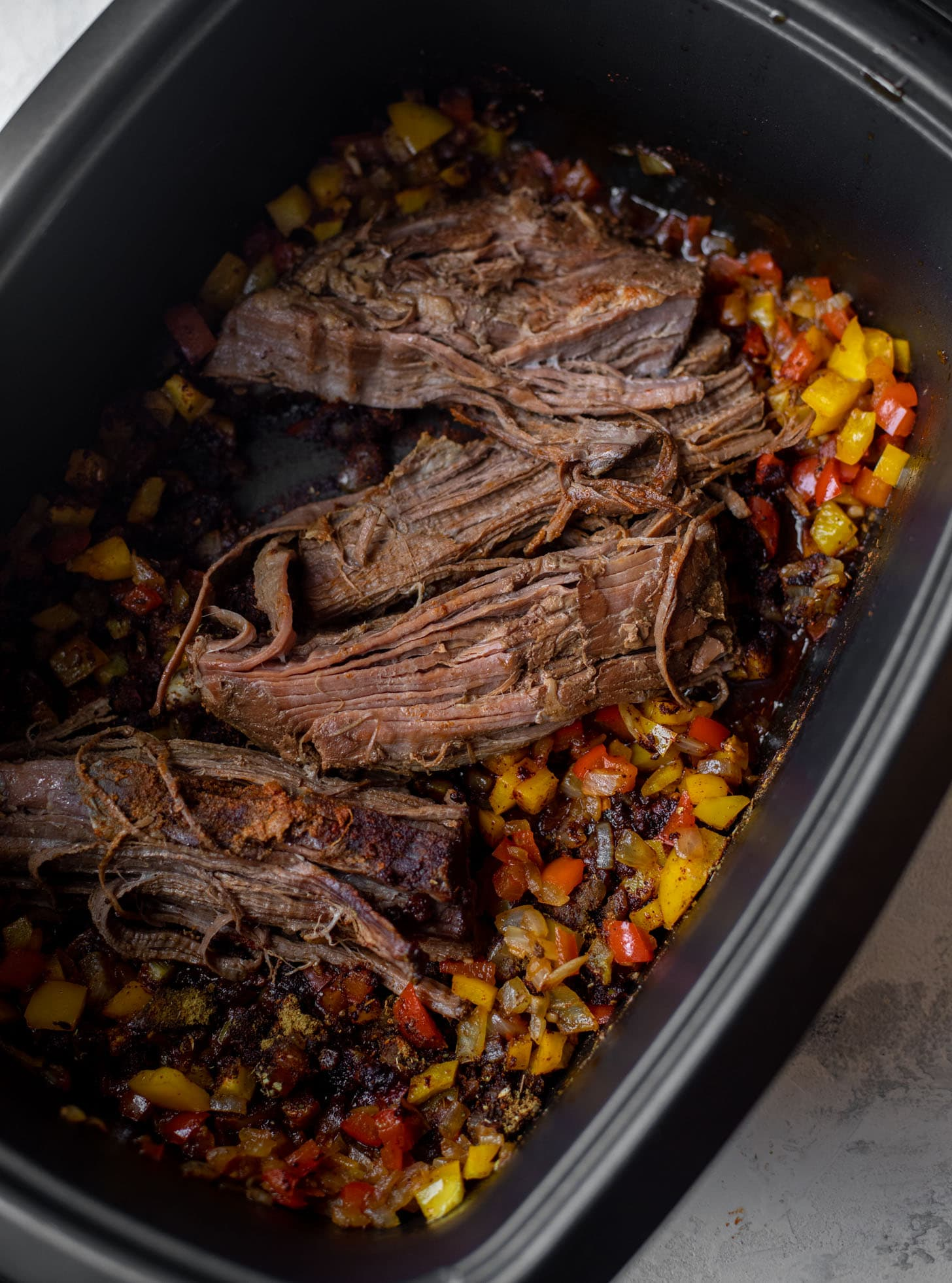 slow cooker with brisket and peppers and onions