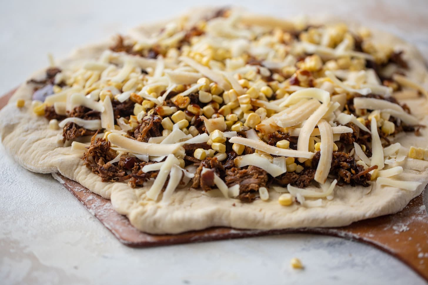 BBQ pulled pork & sweet corn pizza ready for the grill