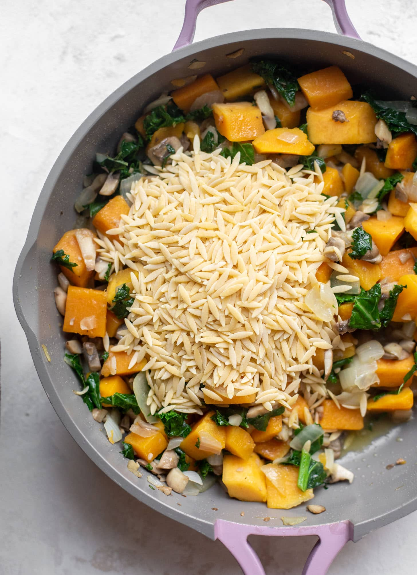 skillet with vegetables and orzo